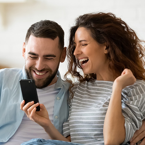 An excited couple looking at their phone