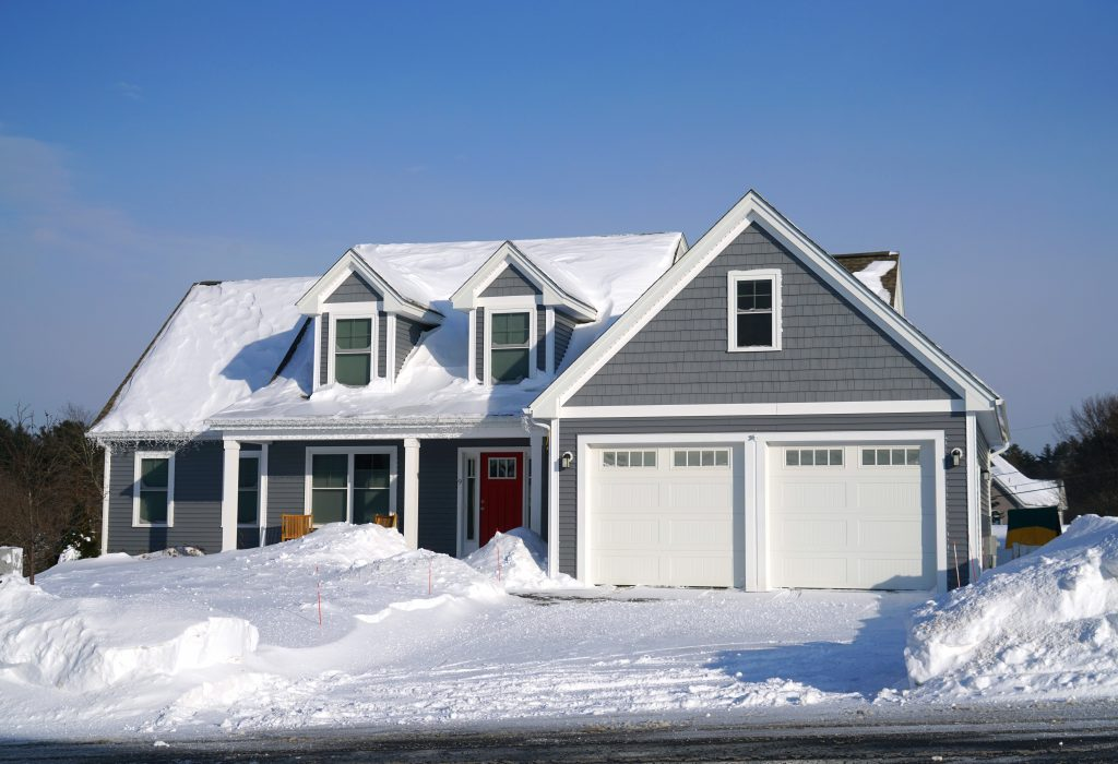 gray craftsman style home with snow on its roof and in the yard
