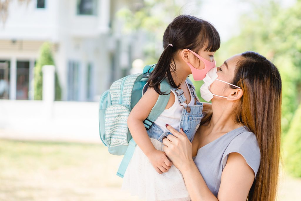 mom holding daughter, both wearing masks and looking at each other