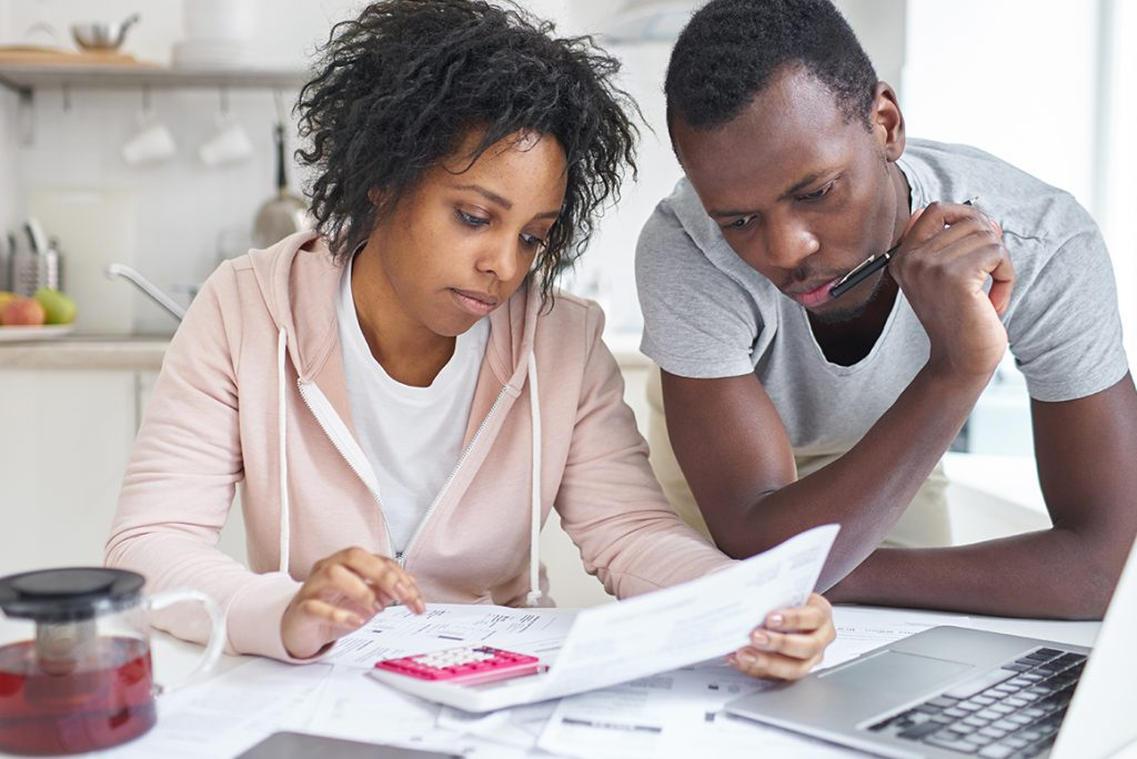 black couple over a computer with paperwork, calculating the cost of selling their home