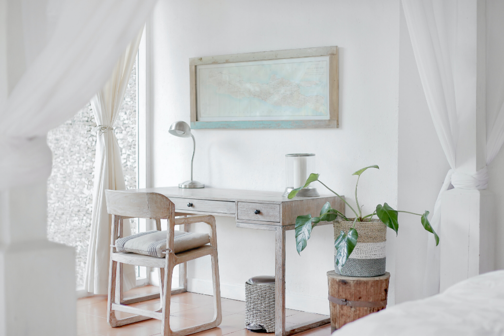 work from home office in bedroom with white desk, walls, and a plant
